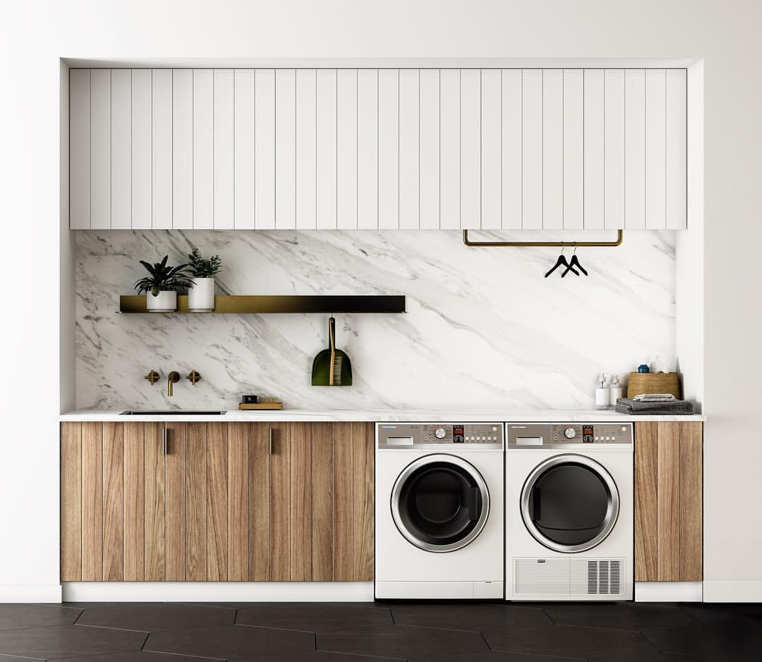Laundry room with marble backsplash, front-load washer and dryer, natural wood cabinets, and a deep utility sink set in neutral white countertops.