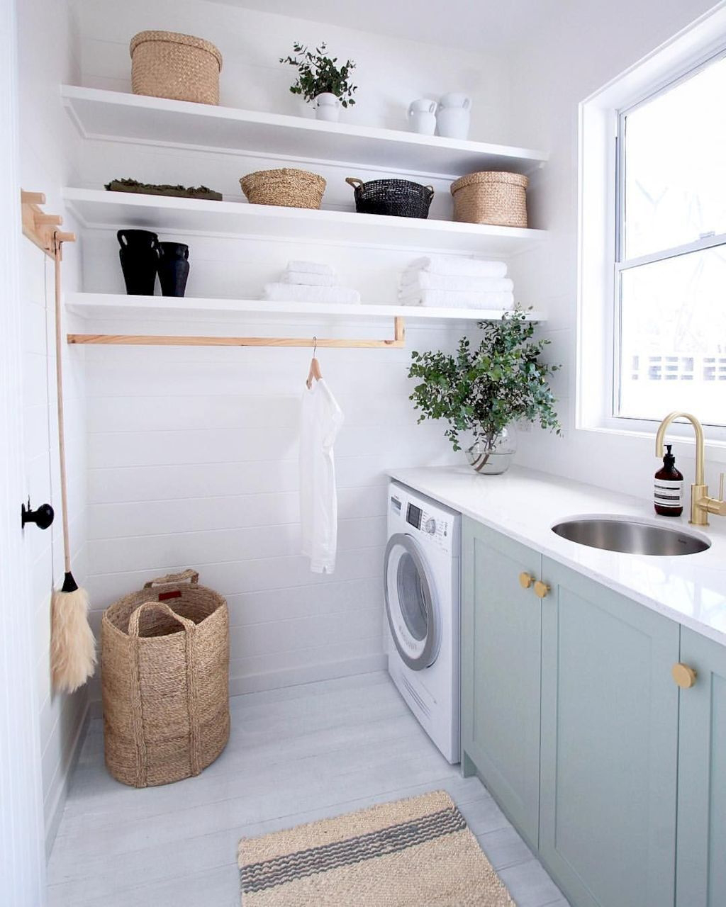 Photo of Laundry room with all white walls and floor, subtle mint cabinets and a single washer/dryer unit.