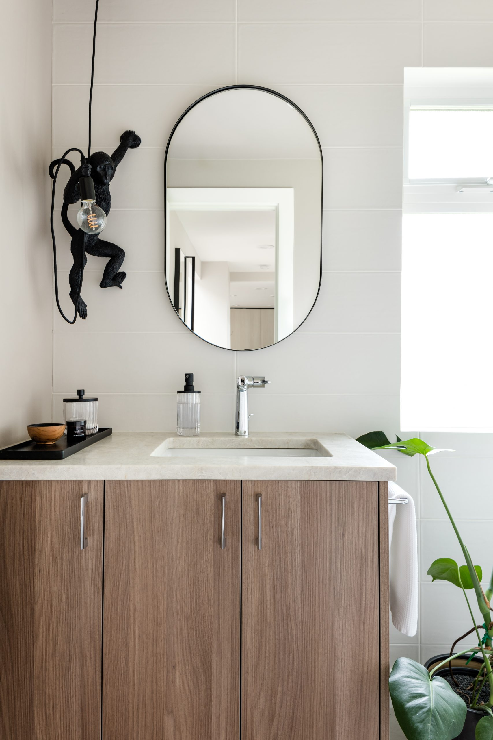 Vanity setup with white walls and natural wood cabinets in Powder Room after shot: half-bath, water closet